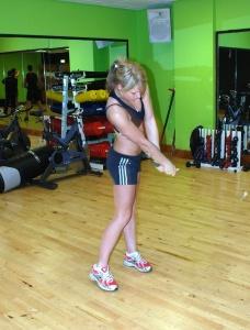 athletic female golfer swinging club